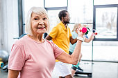 selective focus of cheerful senior woman and her friends exercising with dumbbells at gym