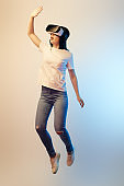surprised brunette woman in virtual reality headset levitating and gesturing on beige and blue