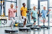 smiling senior multicultural sportspeople synchronous exercising with dumbbells on step platforms at gym