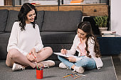 happy mother sitting on floor near cute daughter drawing on paper