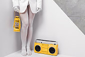 cropped view of woman posing near retro boombox and holding yellow vintage lamp on white and grey