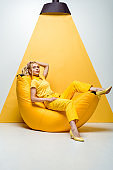 blonde girl sitting on bean bag chair and touching hair on white and yellow