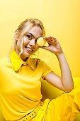 happy blonde girl smiling while covering face with tasty macaron on yellow