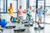 happy multiethnic senior athletes synchronous exercising on step platforms at gym