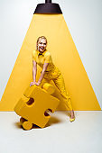 happy blonde woman holding big soft puzzle piece on white and yellow