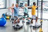 selective focus of senior multicultural athletes synchronous exercising on step platforms at gym