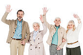 cheerful retired people waving hands isolated on white