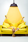 happy blonde woman lying upside down on sofa on white and yellow