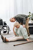 retired husband standing near upset wife sitting on floor