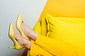 cropped view of woman in heels near pillows on white and yellow