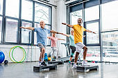 joyful senior multicultural athletes synchronous exercising on step platforms at gym