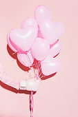 cropped view of woman in boxing glove holding balloons on pink background