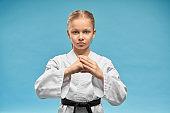 Karate girl with black belt practicing hands position.