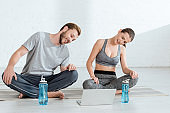 smiling man and woman looking at laptop while sitting in easy poses near sports bottles