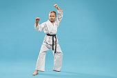 Girl in kimono with black belt practising karate.