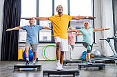 smiling senior multicultural athletes synchronous exercising on step platforms at gym