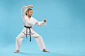 Side view of child standing in karate stance in studio