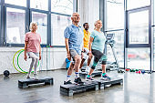 senior multicultural athletes synchronous exercising on step platforms at gym