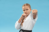 Selective focus of fist of little sports woman in studio