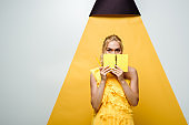 young blonde woman covering face with notebook on white and yellow