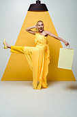 happy blonde woman holding shopping bag while posing on white and yellow
