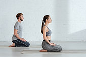 side view of young man and woman practicing yoga in thunderbolt pose