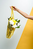 cropped view of  woman holding string bag with flowers on white and yellow