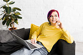 attractive girl with colorful hair sitting on sofa, using laptop while talking on smartphone