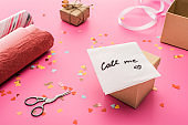 valentines confetti, scissors, card with call me lettering, wrapping paper, gift box on pink background