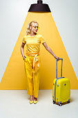 beautiful woman in sunglasses posing with hand in pocket and looking at luggage on white and yellow