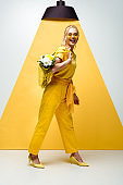 cheerful blonde woman holding string bag with flowers while posing on white and yellow