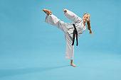 Active sporty girl in kimono kicking with leg in studio