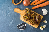 Food and healthy eating concept. Lentils cutlets with carrot and onion on wooden board over dark table.