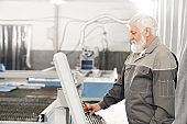 Elderly man working with laser cutting machine on factory.