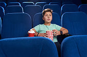 Teenager watching movie in cinema theatre.