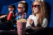 Happy kids watching movie in 3d glasses in cinema.