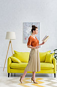 attractive elegant young woman reading book and holding coffee cup in living room