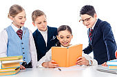 schoolchildren pretending to be businesspeople at desk with schoolgirl reading book Isolated On White