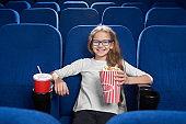 Joyful girl holding popcorn bucket, posing in cinema.