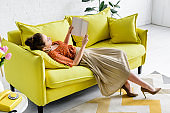 elegant young woman resting on yellow sofa while reading book