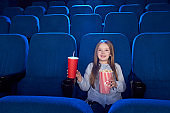 Pretty girl sitting with popcorn bucket in cinema.