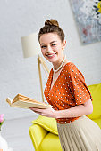 attractive smiling elegant young woman holding book and looking away