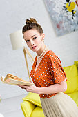 attractive elegant young woman holding book and looking away