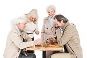 retired friends playing chess near senior women isolated on white