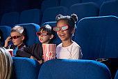 Joyful kids watching movie in 3D glasses, in cinema.