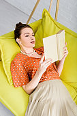 attractive elegant young woman resting on yellow sofa while reading book