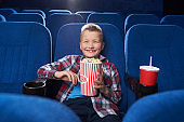 Joyful kid laughing, watching comedy film in cinema.
