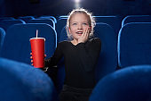Fascinated girl watching movie in theatre.