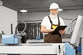 Worker of factory holding folder, observing laser cutter.