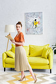 attractive elegant young woman holding book and looking away while standing in living room